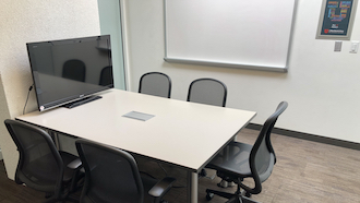 table, 2 chairs, whiteboard, and projector screen