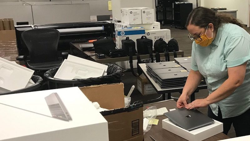 a staff member coding new laptops to distribute to students