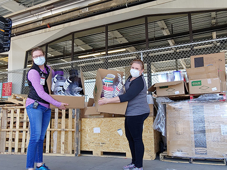Two volunteers accepting a donation of faceshields at the hosptial