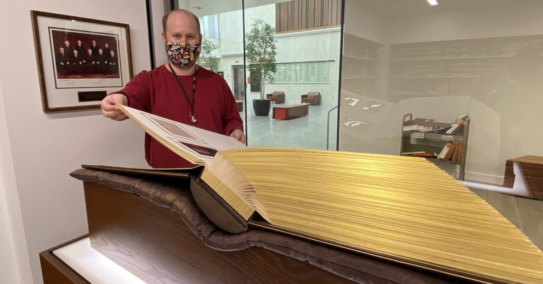 dan standing next to an oversized book. the pages are shiny and ornate.
