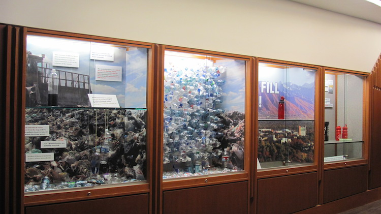 Just Fill It Exhibit consisting of four windows displaying expamples of environmental impact of plastic bottles