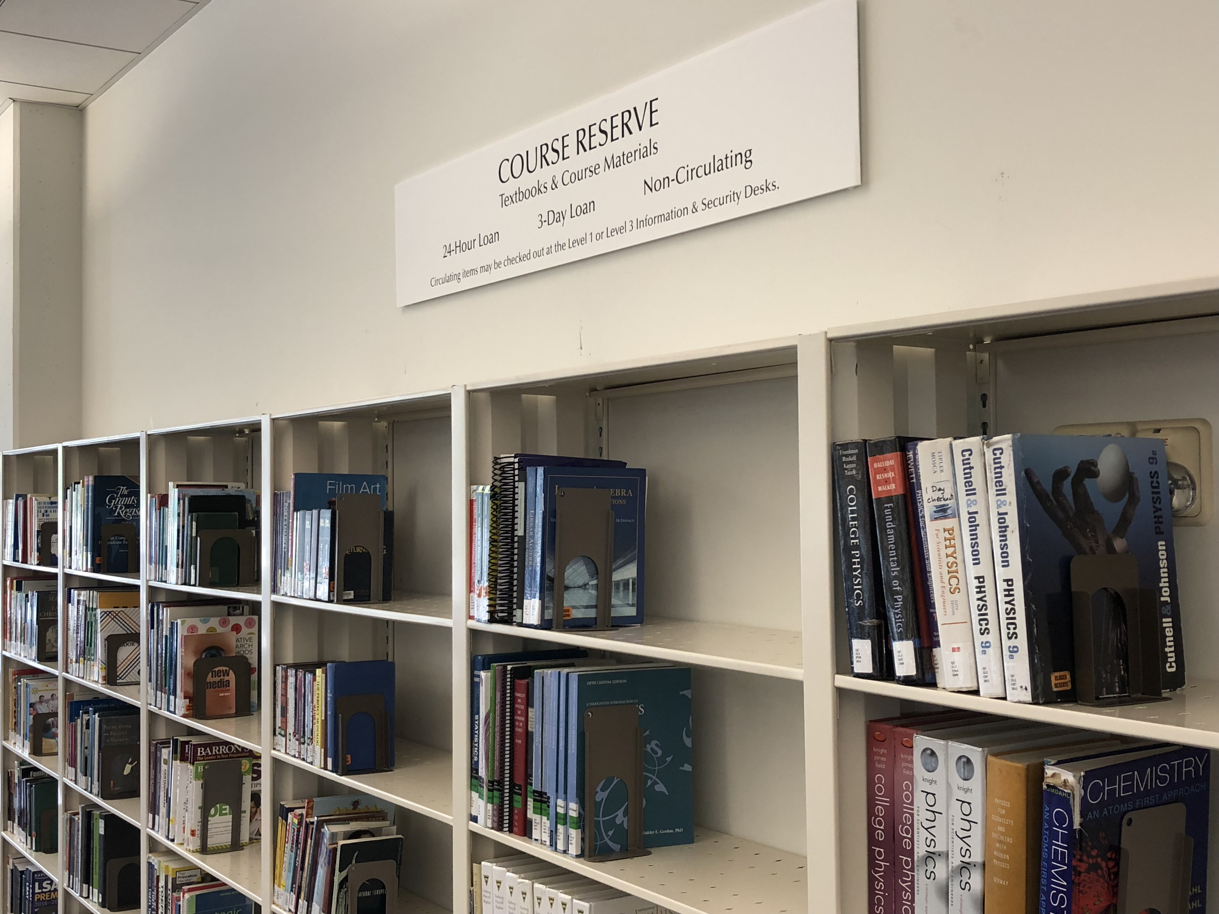 "shelves of Reserve books and sign that reads ""Course Reserves"""
