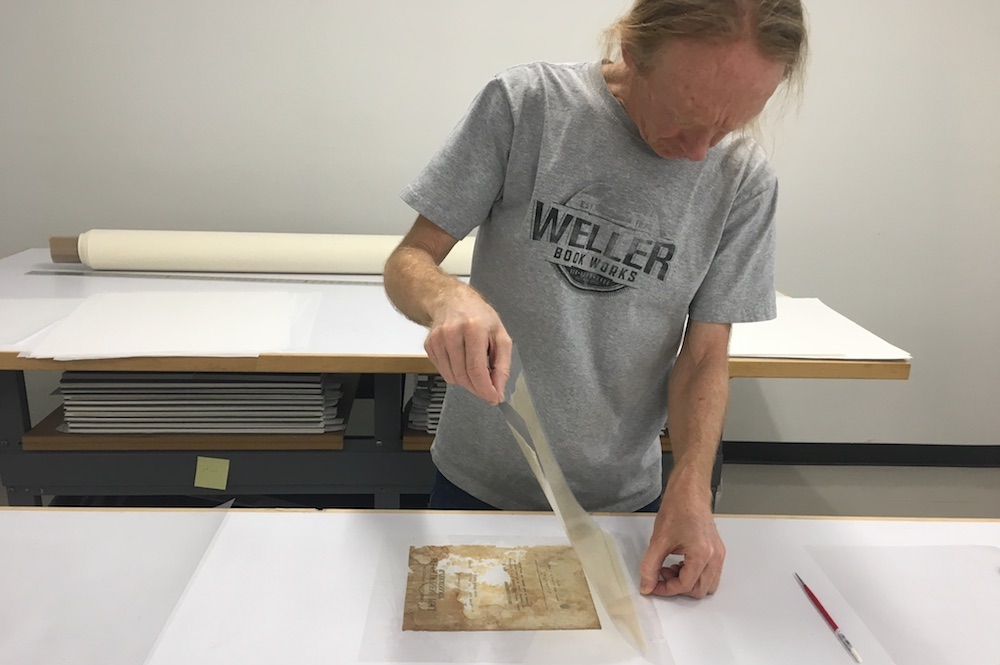 Book Conservator Jeff Hunt applying a lining to one of the pages